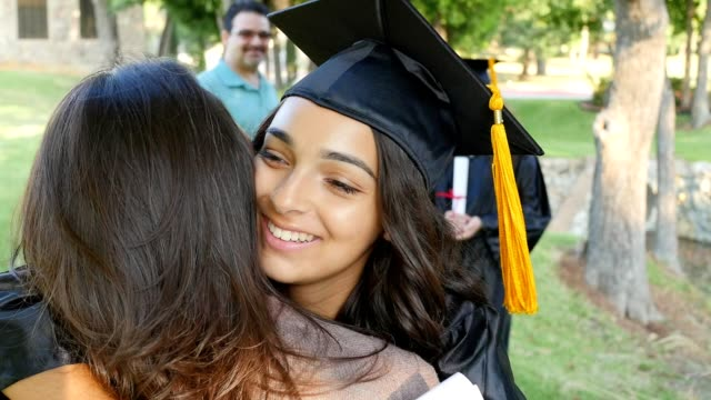 Recent college graduate excitedly hugs her mom after graduation ceremony video