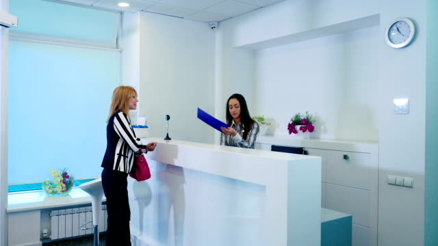 Reception of the cosmetology clinic The woman ask some question in the girl at the reception in cosmetology center. The girl smile and give the form and pencil to the client. The woman ask the question and take the pencil to fill the form. dermatology stock videos & royalty-free footage