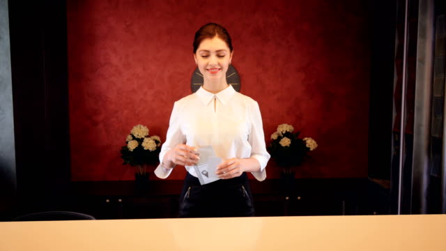 receptionist at hotel reception desk meet guests. 4k. - hotel checkin video stock e b–roll