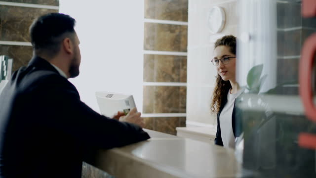 receptionist girl talking with arrived businessman about check-in at reception in hotel. business, travel and people concept - hotel checkin video stock e b–roll