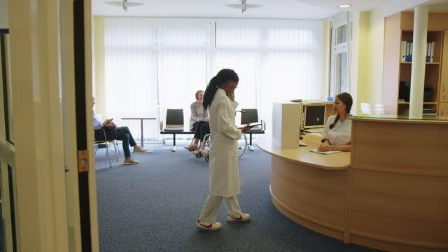 ロビーで医師に報告する受付係 ビデオ