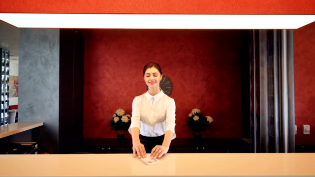 receptionist greeting hotel guest, giving room key. 4k. - hotel checkin video stock e b–roll