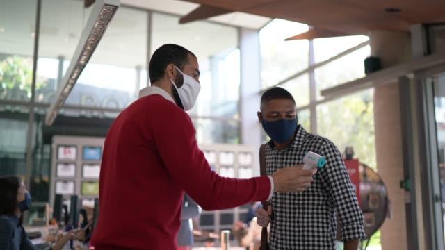 addetto alla reception che misura la temperatura del giovane dipendente all'ingresso dell'ufficio - con maschera facciale - esame università video stock e b–roll