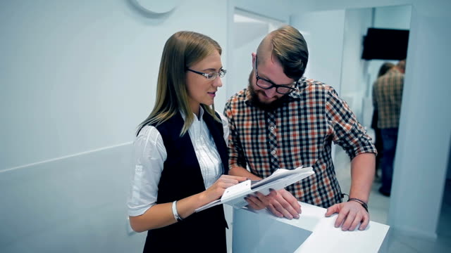 vídeos y material grabado en eventos de stock de recepcionista que muestra la lista de clientes de servicios - recepcionista