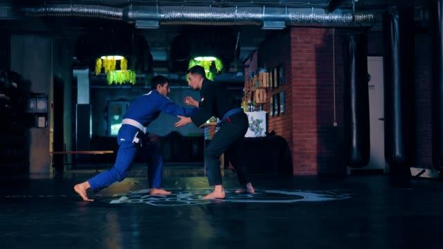vídeos de stock, filmes e b-roll de recepções jiu-jitsu, golpes. técnicas de teste por atletas em um quimono. clube de luta. - artes marciais