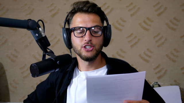 recording studio, close up young man in glasses reads the text into microphone while working on radio video