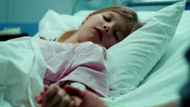 vídeos de stock e filmes b-roll de recovering little girl lying in the hospital bed sleeping, mother holds her hand comforting. emotional family moment. - doença