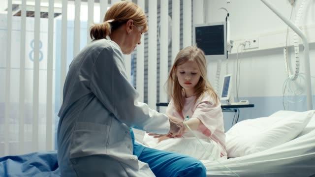 病院のベッドとフレンドリーな女性医師との協議に小さな女の子座って回復。子供の病院の小児病棟。最高品質の医療。 ビデオ
