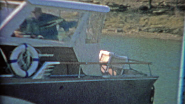 1964: Recreational boat heading out of harbor into the sunny waters. video