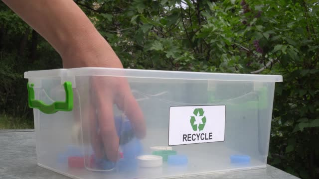 recycle plastic bottle caps and lids. sorting and recycling household waste - coperchio video stock e b–roll