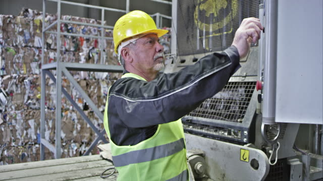 TU recycling facility worker operating the baling press machine video
