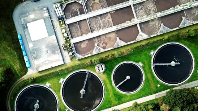 Recycling in Daily Life Aerial shot of sewage treatment plant placed near a river, Denmark.  Aerial view shot with drone. environmental conservation stock videos & royalty-free footage