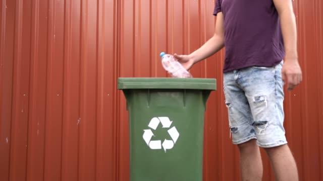 recycling von plastikflaschen, flaschen in den mülleimer stellen - altglas stock-videos und b-roll-filmmaterial