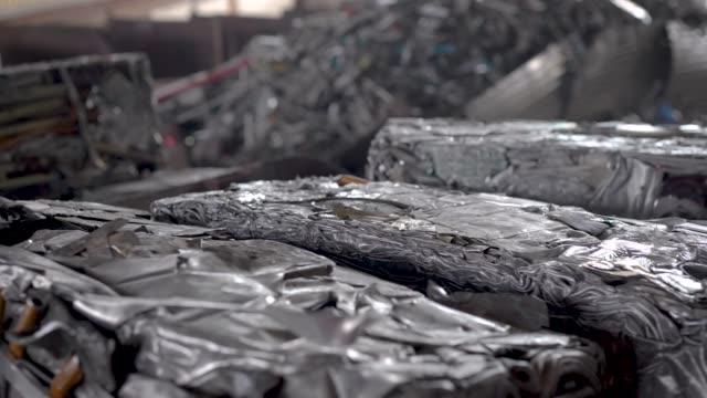 vídeos de stock e filmes b-roll de recycling scrap metal. in the frame briquettes pressed from aluminum waste - aço