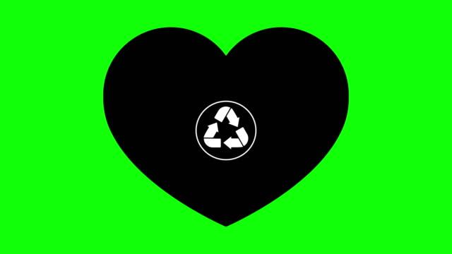 en återvinnings skylt visas i ett svart hjärta på en grön skärm. - recycling heart bildbanksvideor och videomaterial från bakom kulisserna