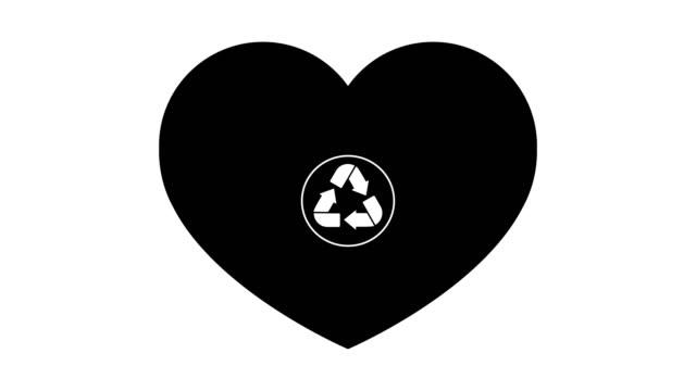 en återvinnings skylt visas i ett svart hjärta på en vit bakgrund. - recycling heart bildbanksvideor och videomaterial från bakom kulisserna