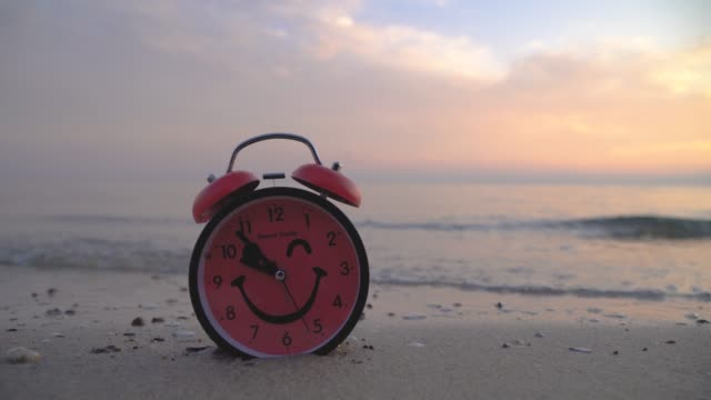 Red alarm clock on sandy beach