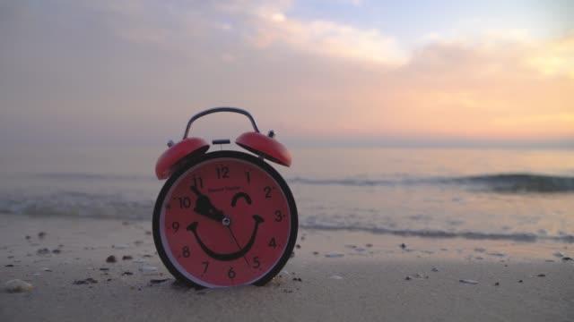 vídeos de stock e filmes b-roll de red alarm clock on sandy beach - climate clock