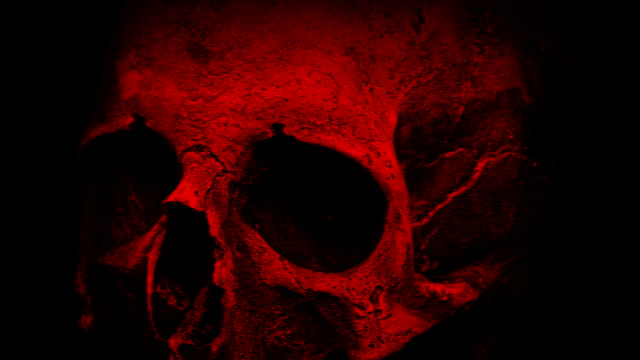 Red Ancient Human Skull Rotating Closeup Loop Closeup of an old human skull turning slowly on black background - Looped for endless playback skull stock videos & royalty-free footage