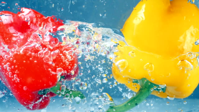 a red and a yellow peppers fall down into water. - paprica video stock e b–roll