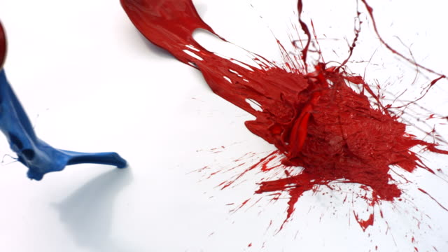 Red and blue paint splattering on white background video