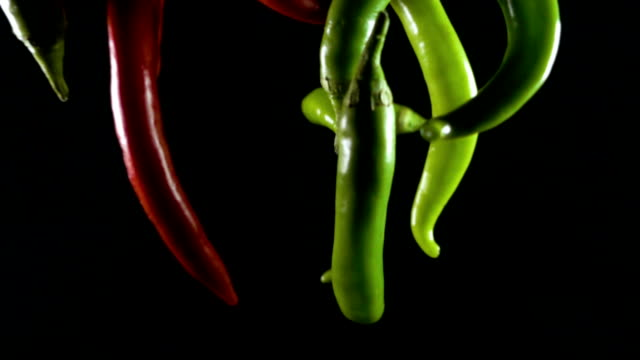 Red and green chili peppers on black background Red and green chili peppers on black background. slow monion competition group stock videos & royalty-free footage