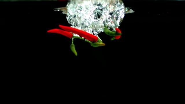 rote und grüne chilischoten falling in water - chilli stock-videos und b-roll-filmmaterial