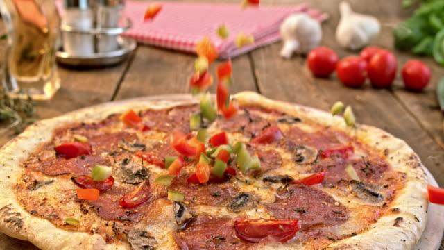 SLO MO rouge et poivrons verts tombent sur une pizza salami - Vidéo