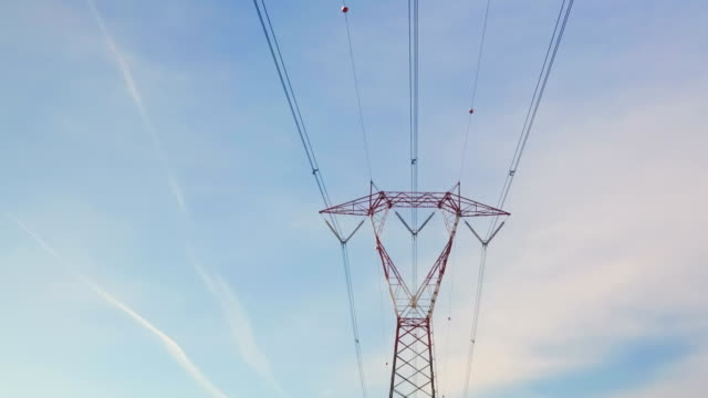 Red And White High Voltage Electricity Pylon Time Lapse on a Blue Cloudy Sky Red And White High Voltage Electricity Pylon Time Lapse on a Blue Cloudy Sky high voltage sign stock videos & royalty-free footage