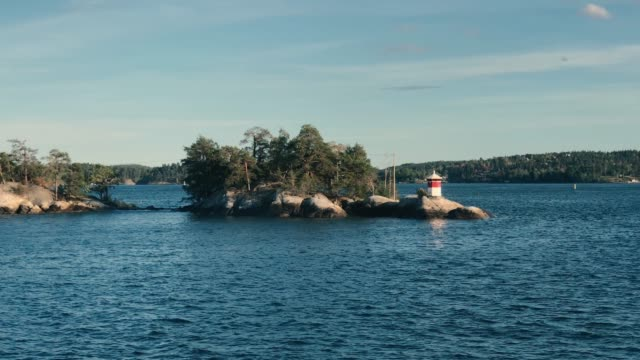vídeos de stock e filmes b-roll de red and white small lighthouse on stockholm archipelago island - arquipélago