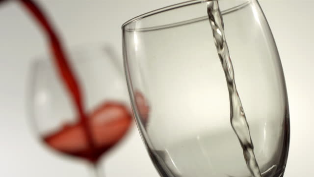 Red and white wine pouring, slow motion video