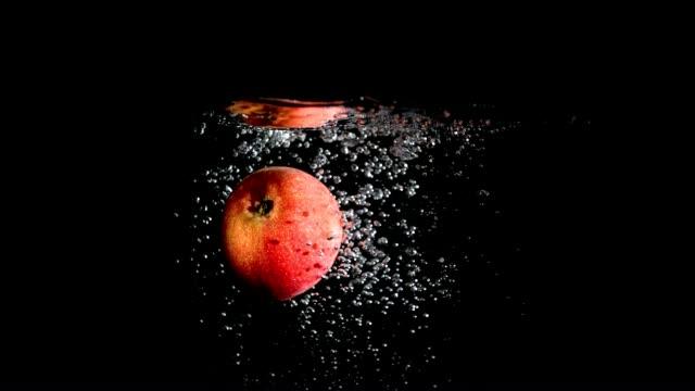 Red apple drop in black water video