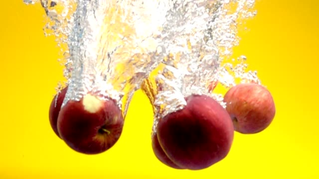 red apples falling into water in slow motion video