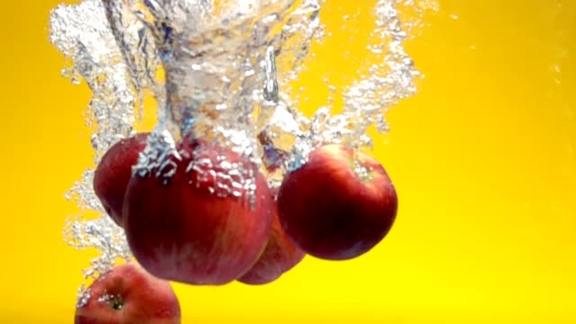 red apples falling under water video