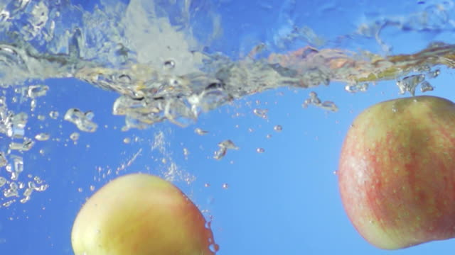 Red Apples Splashing Into Water (Super Slow Motion) video