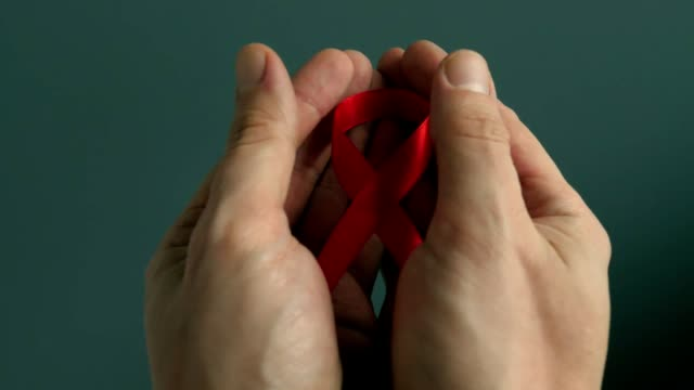 HIV/AIDS red awareness ribbon in the hands. video