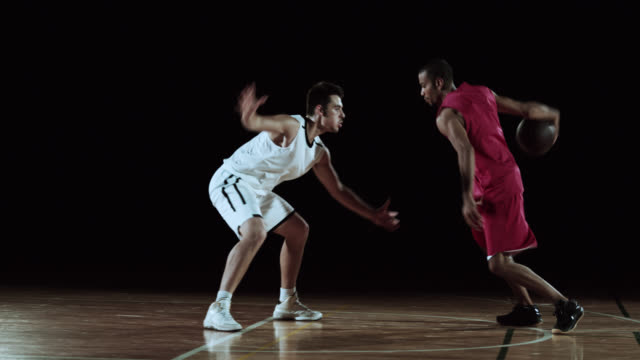 SLO MO of red basketball player dribbling the opponent video