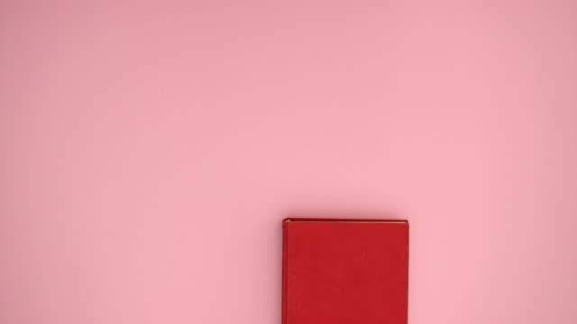 red book open on pink background - stop motion animation - book video stock e b–roll