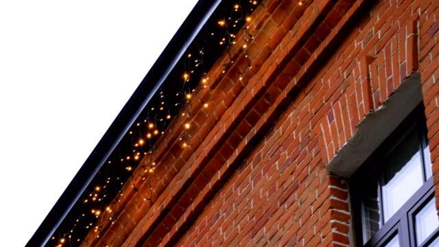 vídeos de stock e filmes b-roll de red brick house with garland lights decorations for christmas or new year. 4k - enfeitado