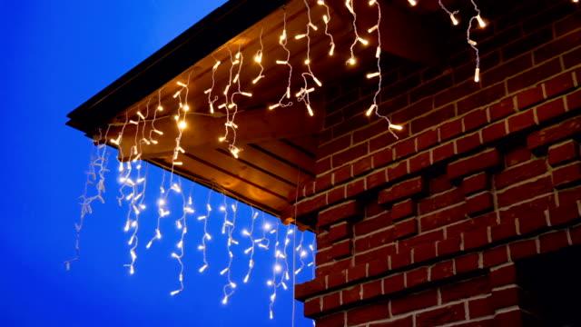vídeos de stock e filmes b-roll de red brick house with garland lights decorations for christmas or new year. hd - enfeitado