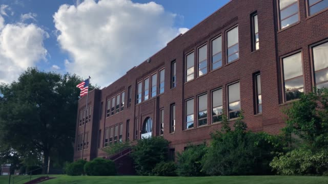 Red Brick School Building with American Flag A daytime summer establishing shot of a typical red brick school building in a small town. American flag waving on flagpole in front. education stock videos & royalty-free footage