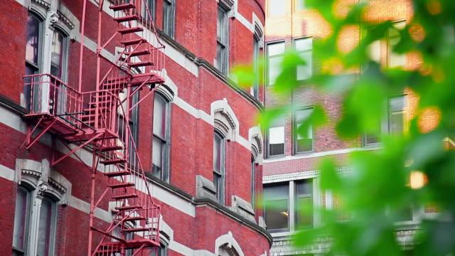 rote gebäude-fassade mit fire escape - sandstein stock-videos und b-roll-filmmaterial