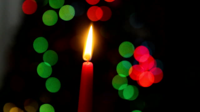 Red candle on a dark background, Christmas candle on bokeh lights background, Christmas evening, New Year, xmas, colored circles, bokeh, closeup video