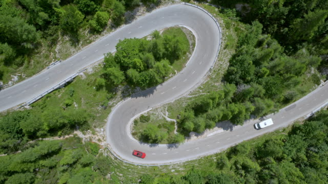 aerial red car driving down the winding mountain road in sunshine - strada tortuosa video stock e b–roll