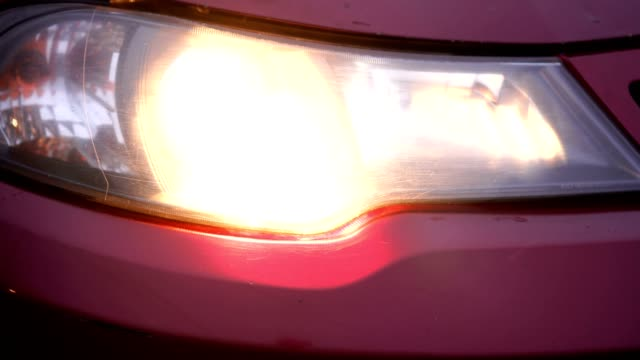 Red car headlight turning on and off. Close-up of details of headlights
