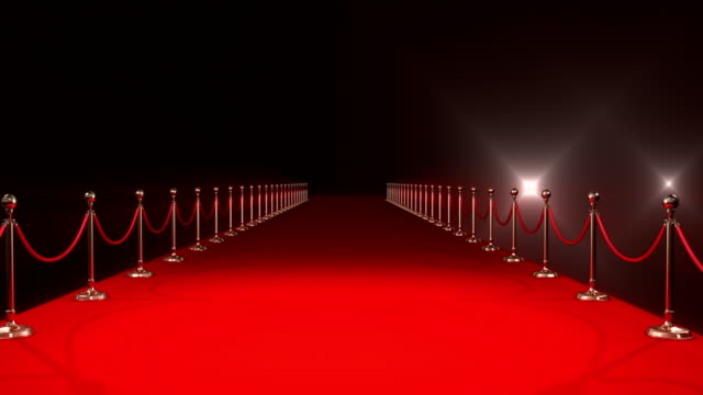 Red carpet with spotlights against black background video