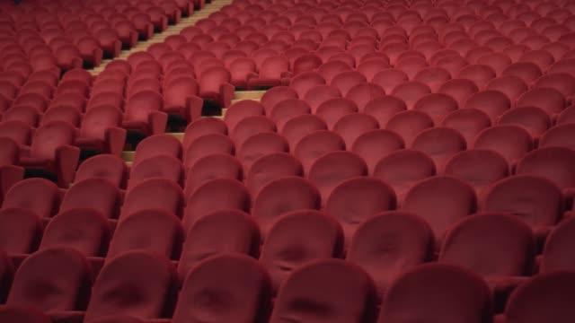 red chairs of the empty theater - mebel do siedzenia filmów i materiałów b-roll