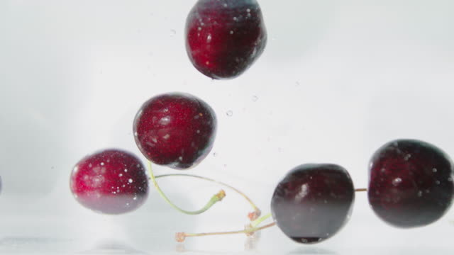 Red Cherries Falling into Water Red cherries falling into crystal clear water cherry stock videos & royalty-free footage