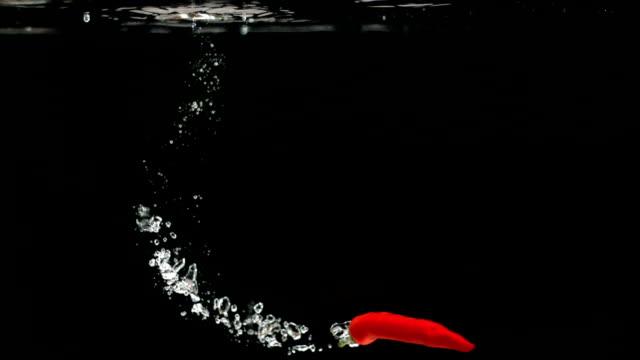 red chili ins wasser fallenden und schwimmende - chilli stock-videos und b-roll-filmmaterial