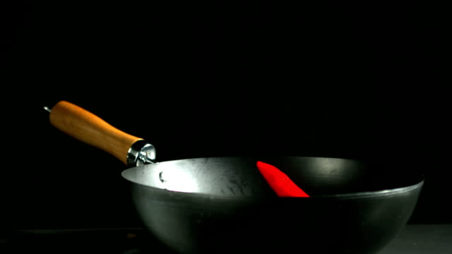 Red chili falling into a wok video